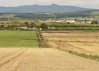 Photograph of arable fields against backdrop of hills