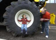 Photograph of a young visitor exploring a combine harvester at Open Farm Sunday