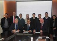 Professor Bob Ferrier (seated right) signs a memorandum of understanding