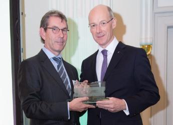 John Swinney MSP, Deputy FM (right), presented the award to Dr Nigel Kerby