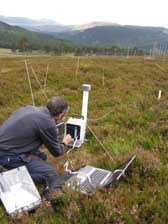 Photograph of a scientist using equipment to measure soil respiration at Invercauld
