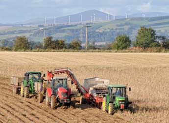 Tractors harvesting potatoes with a windfarm on hills in the distance